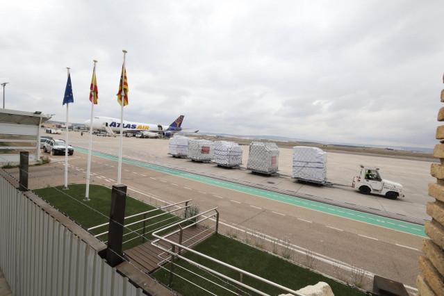 Un trabajador recoge el cargamento del avión (al fondo) que hoy en torno a las 11.30 horas de la mañana ha aterrizado en Zaragoza con 300.000 mascarillas quirúrgicas y 75.000 buzos de protección donados por Inditex al gobierno de España dentro de la lucha