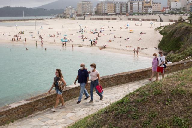 Ciudadanos pasean junto a la playa de Rapadoira de Foz, en la comarca gallega de A Mariña (Lugo).