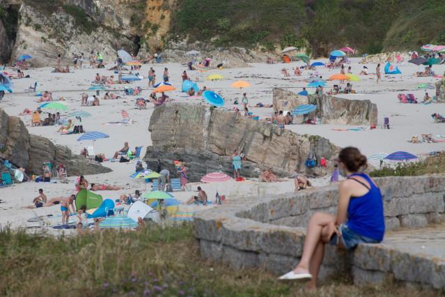 Una persona sentada frente a la playa en A Mariña (Lugo/Galicia) a 27 de julio de 2020. La comarca mantiene este domingo 51 casos activos de COVID-19 tras una nueva alta y un nuevo contagio con respecto al sábado.