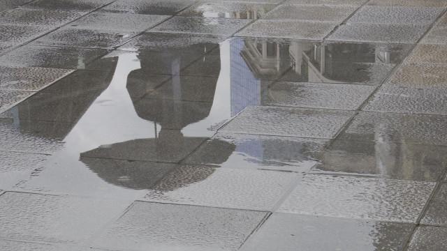 Una persona con paraguas se refleja en un charco provocado por la lluvia esta mañana en Bilbao.