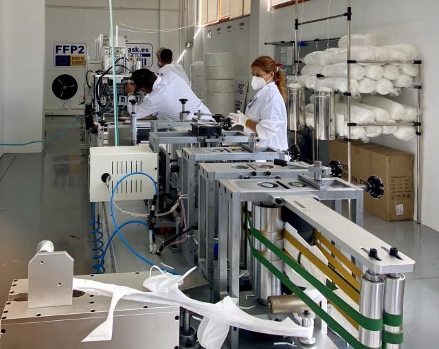 Operarios trabajan en la producción de mascarillas