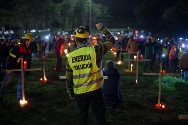 Un trabajador levanta el brazo como signo de protesta durante un velatorio nocturno simbólico convocado por la fábrica de Alcoa, en  en San Cibrao, A Mariña, Lugo, Galicia (España), a 28 de noviembre de 2020. La concentración se produce como signo de prot