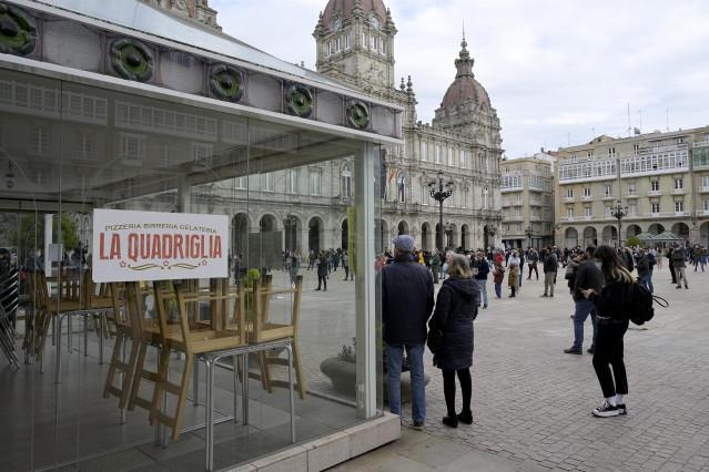 Grupos de personas se concentran en fila de a cuatro en la plaza de María Pita contra las restricciones impuestas al sector hostelero, en A Coruña