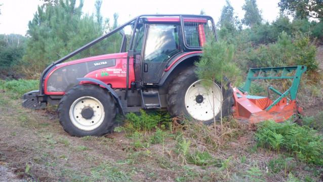 Un tractor desbroza en una finca en Galicia