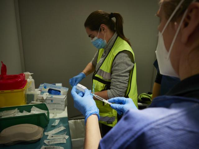 Dos trabajadoras sanitarias en un dispositivo para administrar la vacuna contra la COVID-19