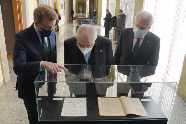 (I-D) El presidente de la Xunta, Alberto Núñez Feijóo; el presidente del Tribunal Constitucional, Juan José González Rivas; y el jefe del Legislativo autonómico, Miguel Ángel Santalices; observan una vitrina en unas jornadas en el Parlamento de Galicia.
