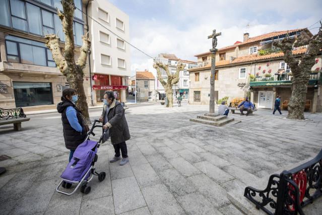 Dos mujeres conversan en una plaza de O Grove, el día en que entra en vigor el cierre perimetral del municipio, a 8 de abril de 2021, en O Grove, Pontevedra, Galicia, (España).  El Comité Clínico de la Xunta de Galicia ha decretado este martes el cierre p