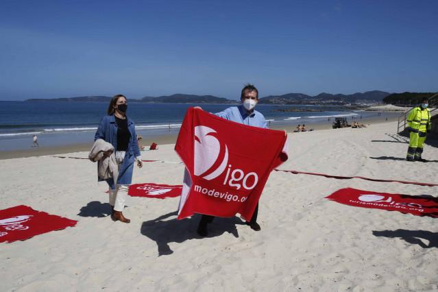 El alcalde de Vigo, Abel Caballero, coloca las cintas en la presentación del sistema de parcelación de playas con cintas separadoras en el arenal de Samil.