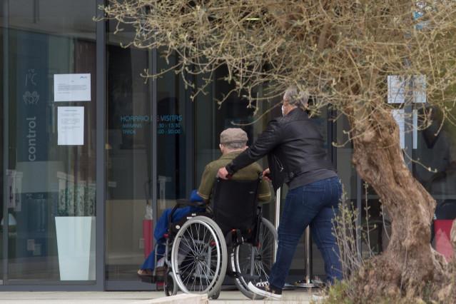 Archivo - Una mujer pasea junto a un anciano en silla de ruedas hacia la residencia Albertia, a 17 de abril de 2021, en Lugo, Galicia (España). Una de las nuevas medidas incluidas en la desescalada de Galicia consiste en la ampliación de las posibilidades