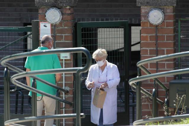 Una trabajadora atiende a un familiar en la puerta de la residencia de As Gándaras de Lugo, en agosto de 2021.
