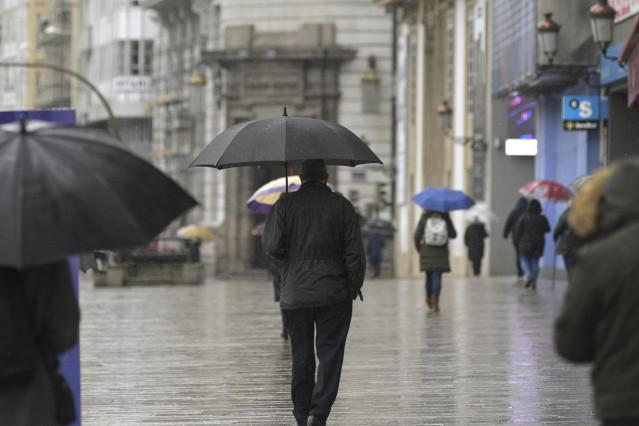 Archivo - Transeúntes caminan protegidos por una vía de A Coruña, Galicia (España), a 20 de enero de 2021. El temporal de nieve y posterior frío provocado por la borrasca 'Filomena' terminará este martes cuando ésta pase el testigo a un nuevo frente, baut